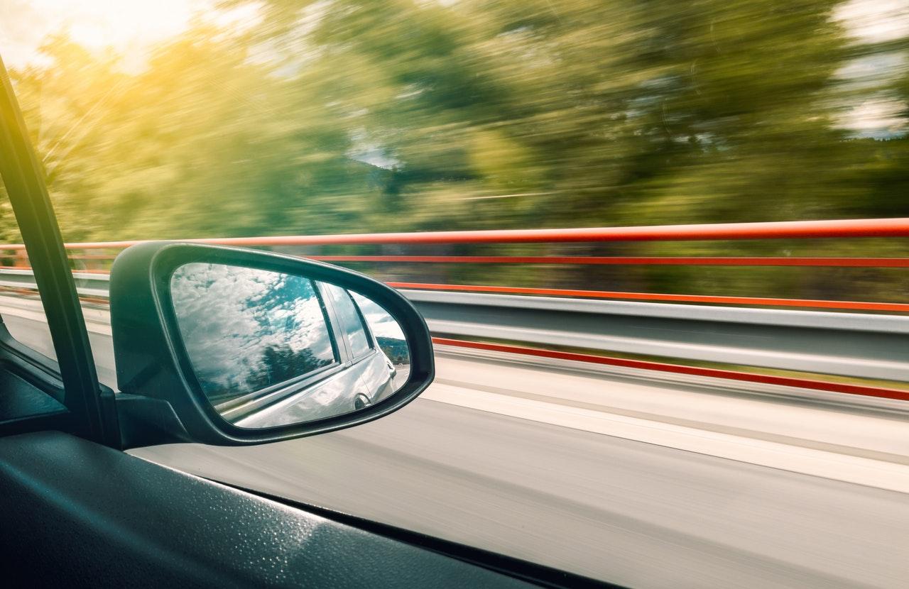 Bil side spejl og udsigt til vejen