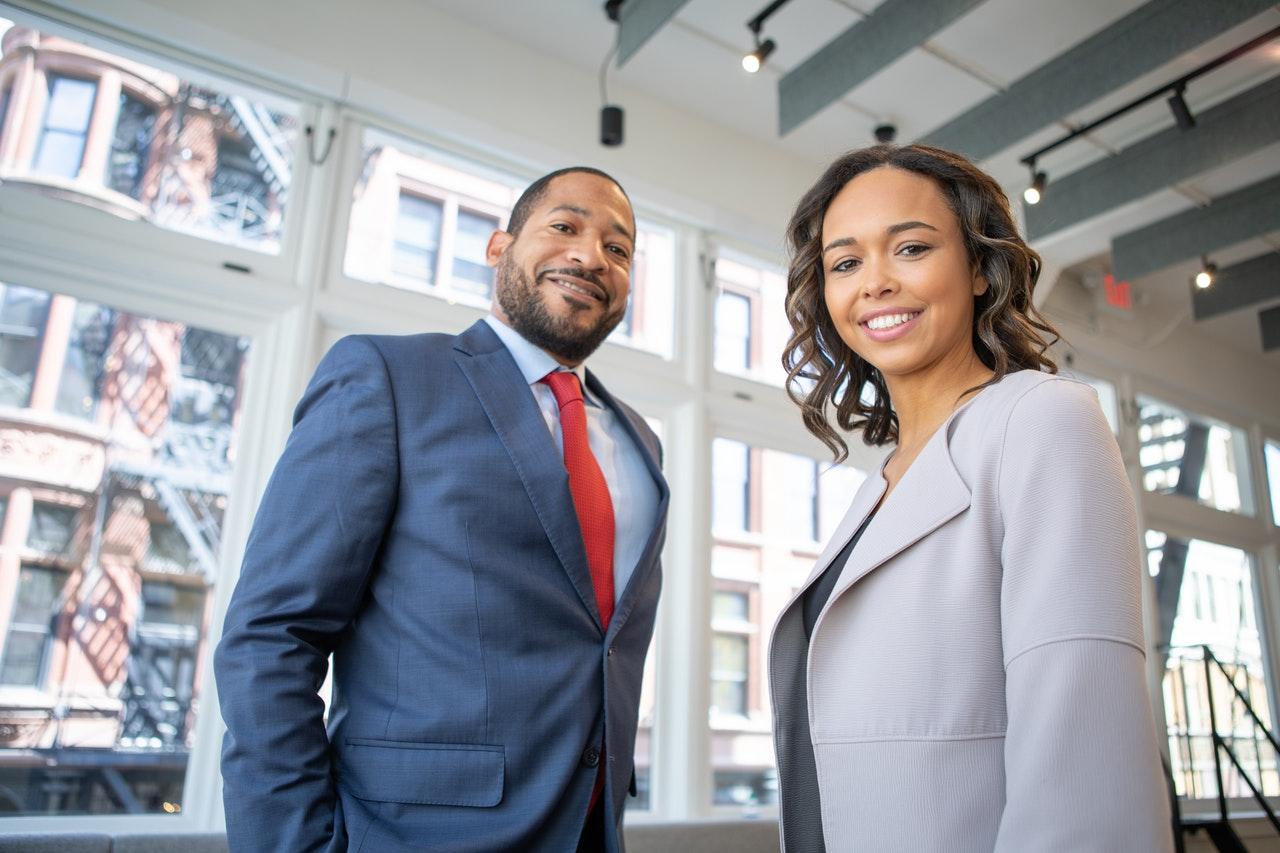 Mand og kvinde smiler på kontor
