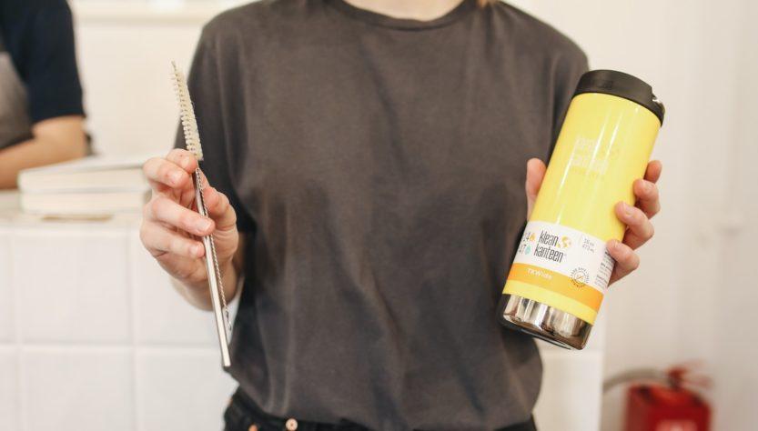 Kvinde holder gul thermokop