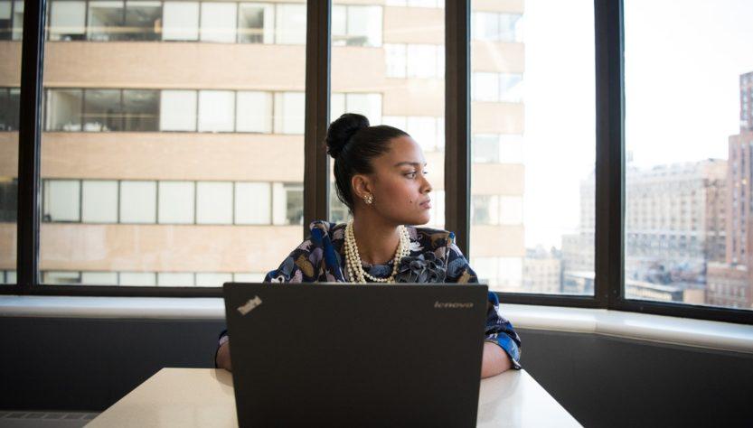 Kvinde arbejder på kontor med store vinduer